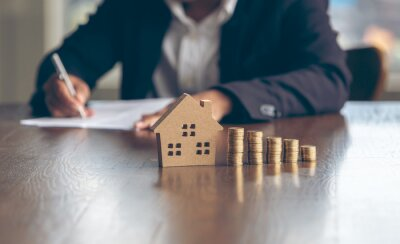 Naklejka Modeling wooden houses and coins and dollars placed on wooden tables,preparation concept for house model purchase and the fastest growing real estate economy,moving home or renting property via agent