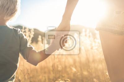 Naklejka Mother little child holding hands walking in a grass field at sunset.