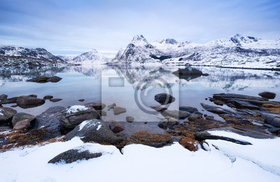 Mountain ridge and ice on the frozen lake surface. Natural landscape on the Lofoten islands, Norway. Water and mountains during sunset. Travel - image