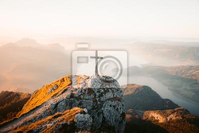 Naklejka Mountain summit cross on alpine peak at sunset