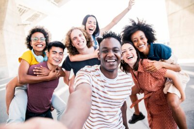 Naklejka Multicultural happy friends having fun taking group selfie portrait on city street - Young diverse people celebrating laughing together outdoors - Happy lifestyle concept