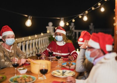 Naklejka Multiracial senior people celebrate christmas together with dinner outdoor while wearing surgical face mask for coronavirus