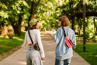 Naklejka Multiracial two women talking and gesturing while walking together