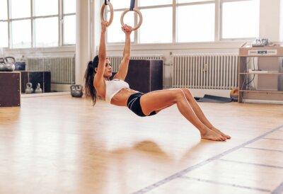 Naklejka Muscular młoda kobieta robi pull-up na ringach