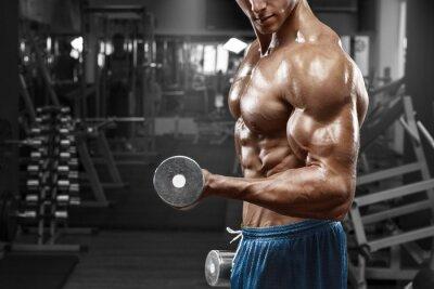 Naklejka Muskularny mężczyzna pracy w siłowni robi ćwiczenia z hantlami na biceps, silny mężczyzna nagi tors abs