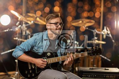 Naklejka muzyk grający na gitarze w studio nad światłami