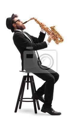 Naklejka Muzyk jazzowy siedzący na fotelu grającym saksofon