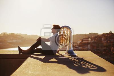Naklejka Muzyk ulicy siedzącej z tubą na świeżym powietrzu o zachodzie słońca. Tło miasta Europy