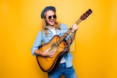 Naklejka Muzyka to mój styl życia! Podekscytowany i beztroski muzyk ubrany w ubranie i okulary gra na gitarze akustycznej i śpiewa piosenkę