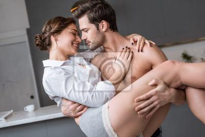 Naklejka namiętny mężczyzna trzyma w ramionach uśmiechnięte dziewczyny w domu