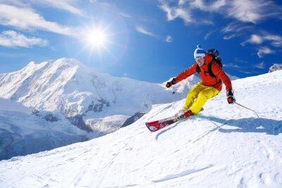 Naklejka Narciarz narciarstwo zjazdowe w wysokich górach przeciw błękitne niebo