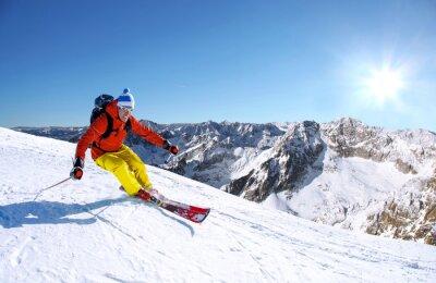 Naklejka Narciarz narciarstwo zjazdowe w wysokich górach przed zachodem słońca
