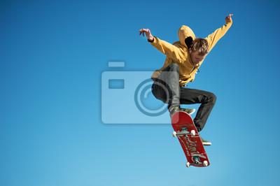 Naklejka Nastoletnie skateboarder robi ollie trick na tle niebieskiego nieba gradientu