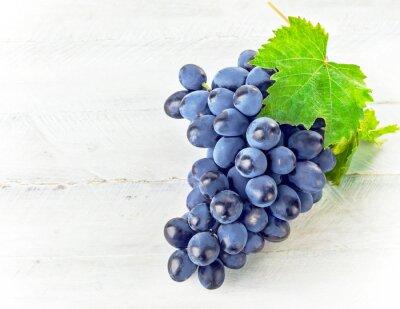Naklejka Niebieski winogron z zielonym liściem na desce