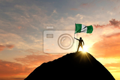 Naklejka Nigeria flag being waved at the top of a mountain summit. 3D Rendering