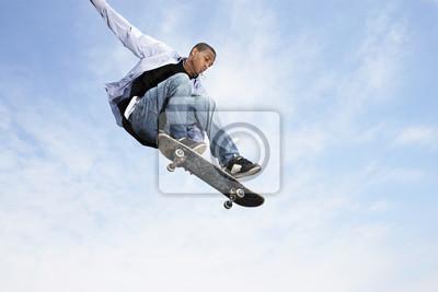 Naklejka Niski k? T widzenia m? Odego cz? Owieka na skateboard w powietrzu przeciwko pochmurne niebo
