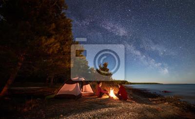 Naklejka Nocne biwakowanie na brzegu. Mężczyzna i kobieta wycieczkowicze mają odpoczynek przed namiotem przy ogniskiem pod wieczór niebem pełnym gwiazd i Mlecznym sposobem na błękitne wody i lasu tle. Koncepcj