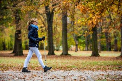 Naklejka Nordic walking - middle-age woman training in city park