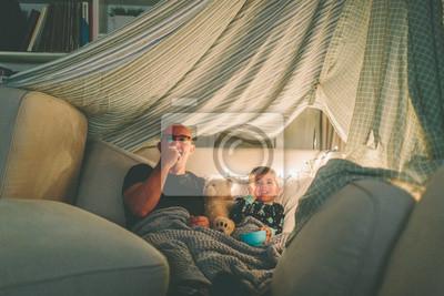 Naklejka Ojciec i syn oglądają film w forcie i jedzą popcorn.