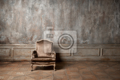 Naklejka old armchair against a vintage wall