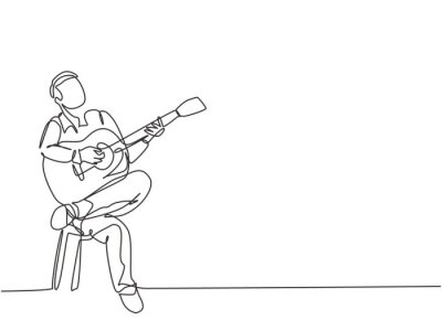 Naklejka One single line drawing of young happy male guitarist playing acoustic guitar while sitting on chair. Modern musician artist performance concept continuous line draw design vector illustration graphic