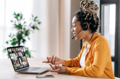 Naklejka Online business group brainstorm by video conference. Satisfied african american young woman, communicates with business partners by video call uses laptop, multiracial colleagues on a laptop screen