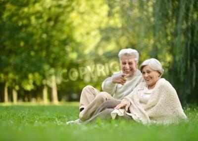 Naklejka Osoby w podeszłym wieku para siedzi razem na trawie w parku jesienią