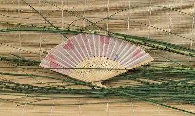 Naklejka Otwórz wentylator z zielonych liści leży na maty bambusowe