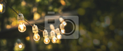 Naklejka outdoor party string lights hanging in backyard on green bokeh background with copy space