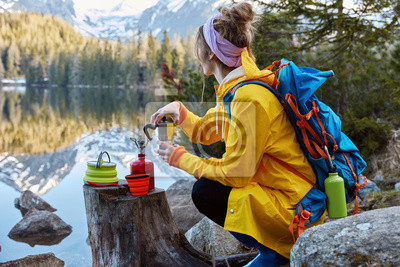 Naklejka Outdoor view of young woman uses tourist equipment for making coffee, has portable gas stove on stump, focused in distance, admires scenic lakescape, rock mountains reflect in water. Tourism concept