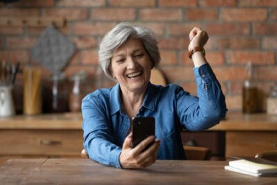 Naklejka Overjoyed aged senior latin grandmother pensioner yell yes super celebrate winning mobile phone game. Happy elderly female sit at kitchen table read email excited with great sale discount at web shop