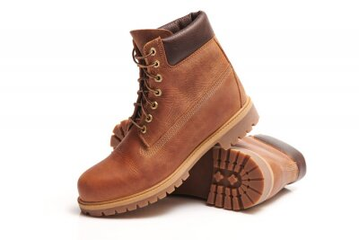 Naklejka Pair of Mens leather brown waterproof boots for winter or autumn hiking isolated on white background. Mens fashion, trendy footwear. Close up view.