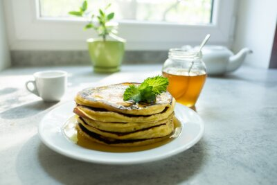 Naklejka Pancakes heap with sprig of mint and maple syrup