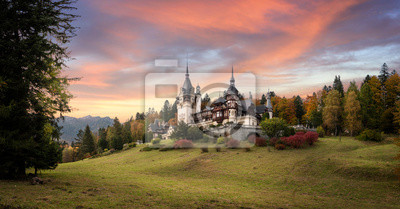 Naklejka Panorama of Peles Castle, Romania. Beautiful famous royal castle and ornamental garden in Sinaia landmark of Carpathian Mountains in Europe at sunset. Former Home Of The Romanian Royal Family.
