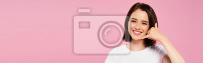 Naklejka panoramic shot of beautiful smiling girl showing call me gesture isolated on pink