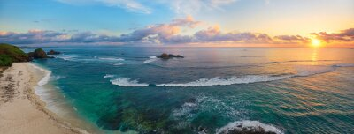 Naklejka Panoramiczny widok na tropikalnej plaży o zachodzie słońca z surferów.