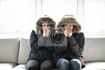 Naklejka Para ma zimno na kanapie w domu z płaszczem zimowym