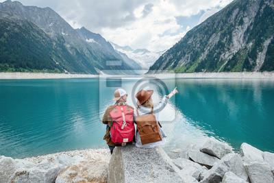 Naklejka Para podróżników patrzy na górskie jezioro. Koncepcja podróży i aktywnego życia z zespołem. Przygoda i podróże w regionie górskim w Austrii. Podróż - obraz