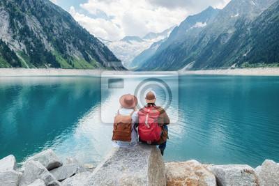 Naklejka Para podróżników wygląda na górskie jezioro. Podróż i koncepcja aktywnego życia z zespołem. Przygoda i podróże w regionie gór w Austrii