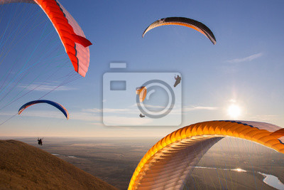 Naklejka Paraglide with a paraglider in a cocoon against the background of fields of the sky and clouds. Paragliding Sports