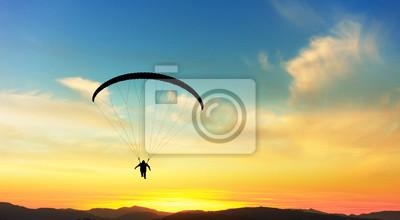 Naklejka Paralotniarstwo w chmurach o zachodzie słońca.
