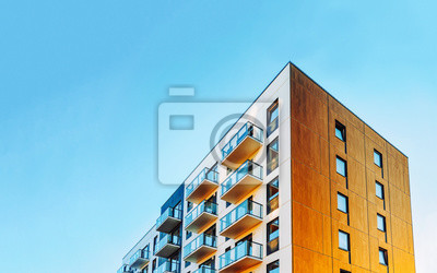 Naklejka Part of Modern residential apartment with flat building exterior. Detail of New luxury house and home complex. Fragment of City Real estate property and condo architecture. Copy space. Blue sky