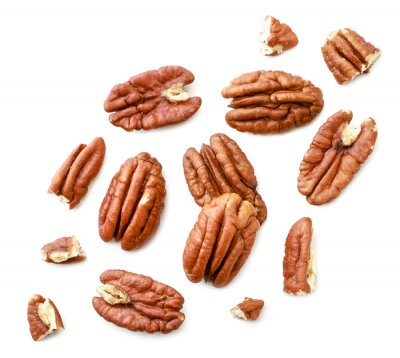 Naklejka Peeled pecans with broken halves and pieces on a white background. The view from top.
