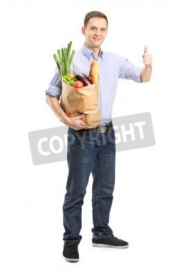 Naklejka Pełna długość portret mężczyzny gospodarstwa torbę z zakupami i daje kciuk w górę na białym tle