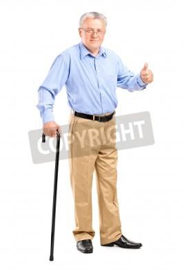 Naklejka Pełna długość portret starszego mężczyzny trzyma laskę i daje kciuk w górę na białym tle