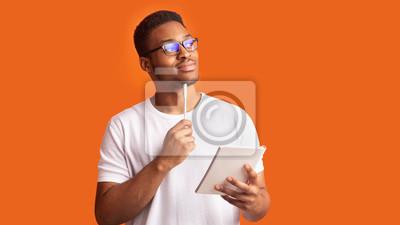 Naklejka Pensive afro man portrait on orange background