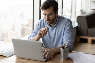Naklejka Pensive serious young Caucasian man sit at desk in office look at laptop thinking pondering. Thoughtful male employee work online on computer make plan or decision, brainstorm at workplace.