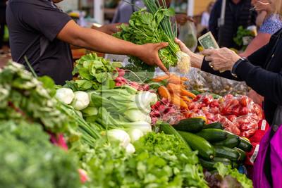Naklejka People buying fresh organic vegetables from local farmers in the city bazaar