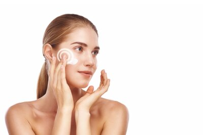 Naklejka Perfect skin. Beautiful young woman applying cosmetic cream on her face while standing against white background. Beauty products
