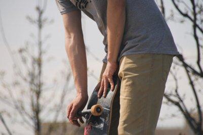 Naklejka person holding a skateboard